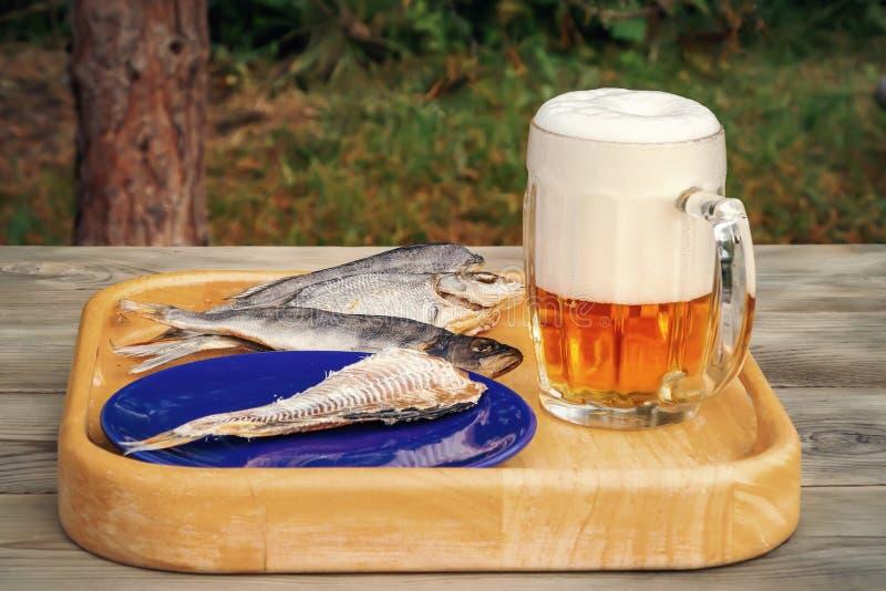 Mok licht bier en droge vissen op een houten lijst in een de zomerdag in openlucht - foto, beeld stock foto's