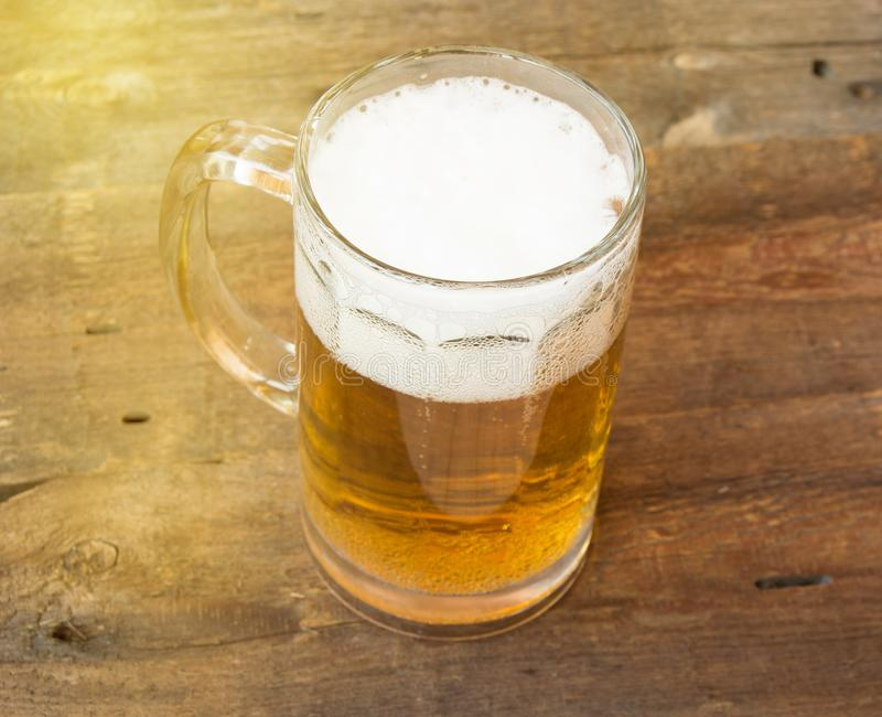 Mok licht bier met schuim op donkere uitstekende houten raad royalty-vrije stock foto