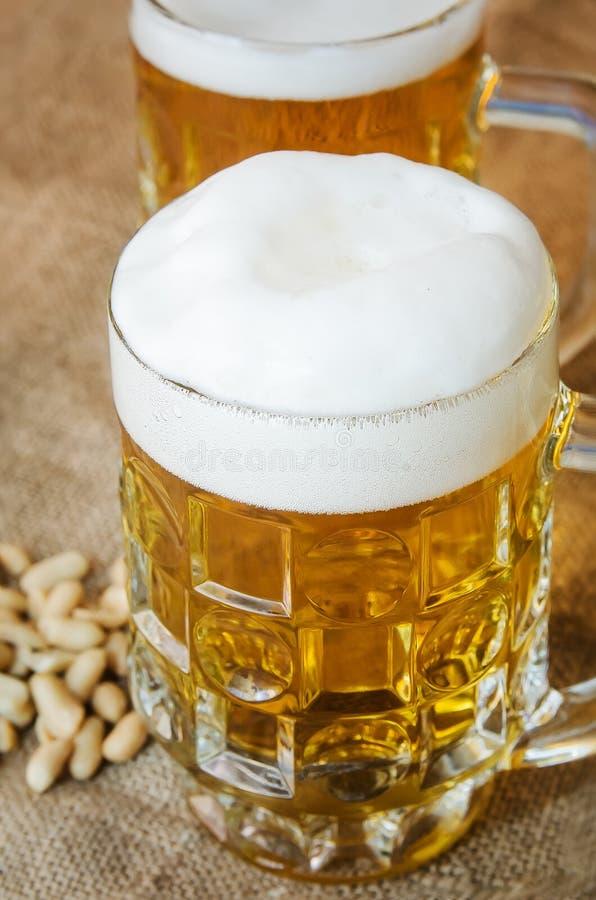 Mok met bier en gezouten pinda's op de lijst royalty-vrije stock foto