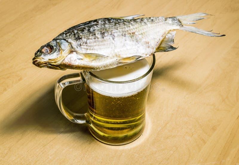 Mok met bier en vissen op de lijst stock foto