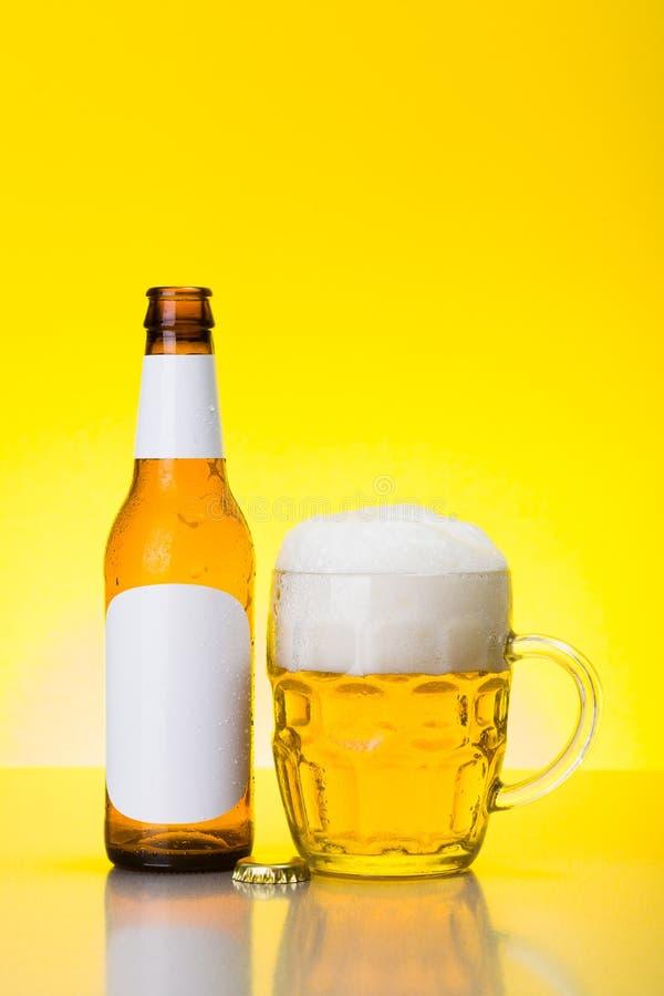 Mok met schuimend bier en lege fles stock fotografie