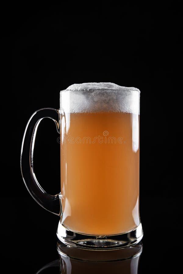 Mok schuimend die bier op donkere achtergrond wordt ge?soleerd stock foto
