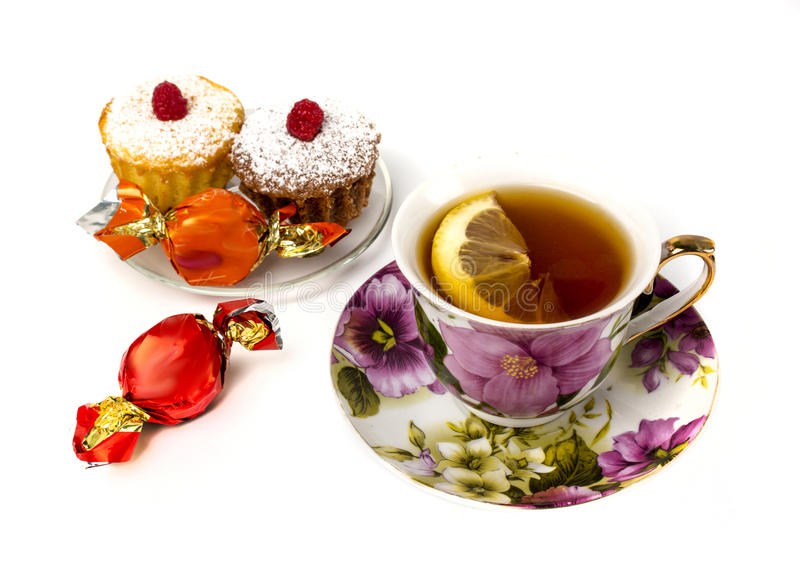Mok thee met citroen en en twee cupcakes royalty-vrije stock afbeeldingen