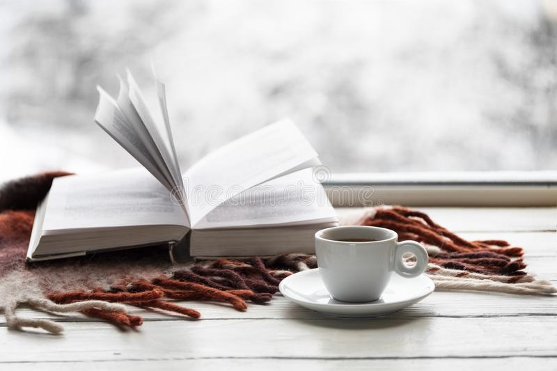 Mok van koffie en geopend boek met warme plaid op witte vensterbank tegen sneeuwlandschap van buiten royalty-vrije stock afbeelding