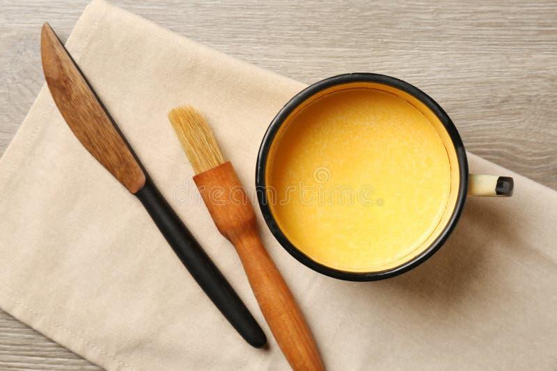 Mok van smeltend boter, borstel en mes op houten lijst stock foto