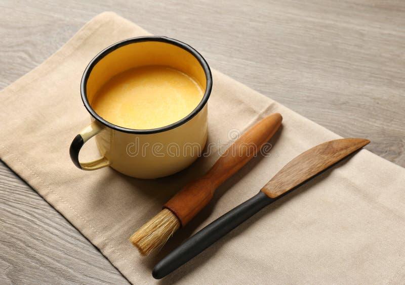 Mok van smeltend boter, borstel en mes op lijst stock afbeeldingen