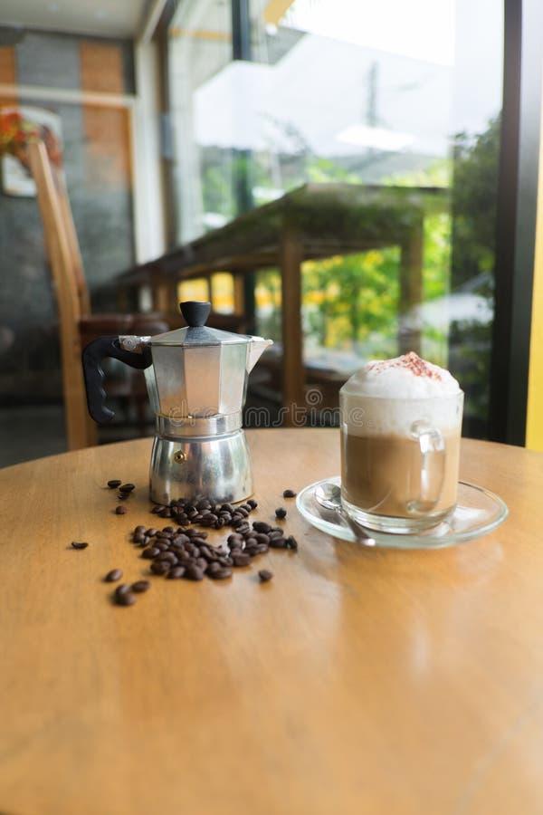 moka罐和一杯咖啡用烤咖啡豆 免版税库存图片