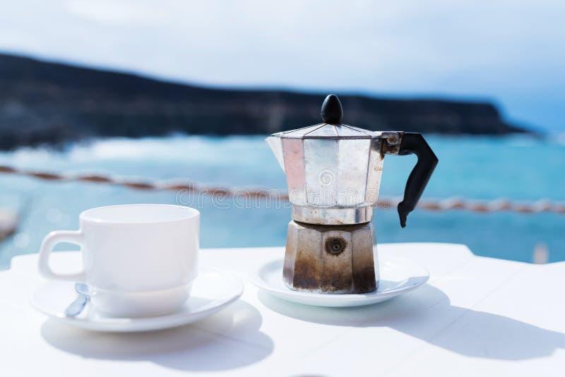 Moka罐浓咖啡制造商和咖啡在桌上的与海岸线和海洋在背景中 免版税库存图片