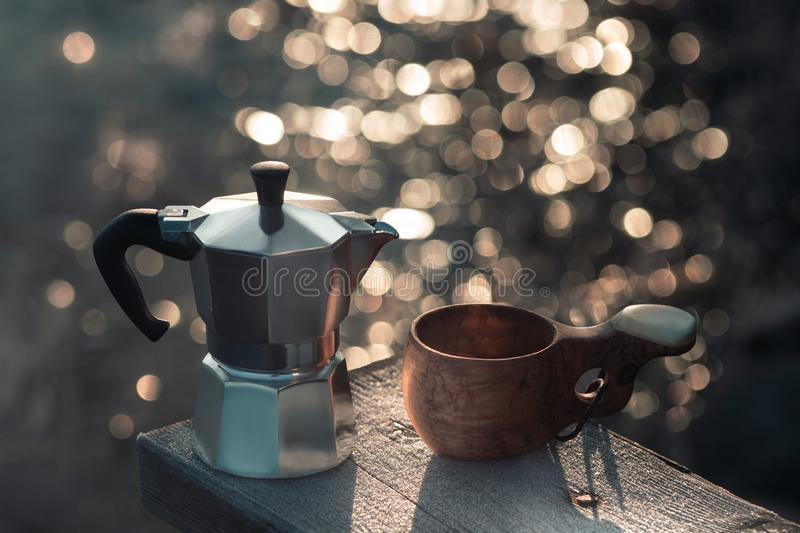 A moka geyser coffee maker and a wooden mug are on the bench. A moka geyser coffee maker and a wooden mug are on the bench royalty free stock photography