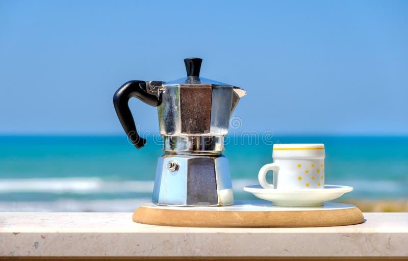 Moka pot coffee maker sea background italian breakfast.  royalty free stock photography