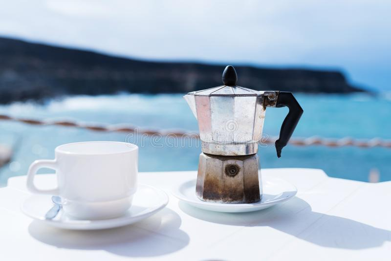 Moka pot espresso maker and cup of coffee on table with coastline and ocean in background. On sunny day royalty free stock image