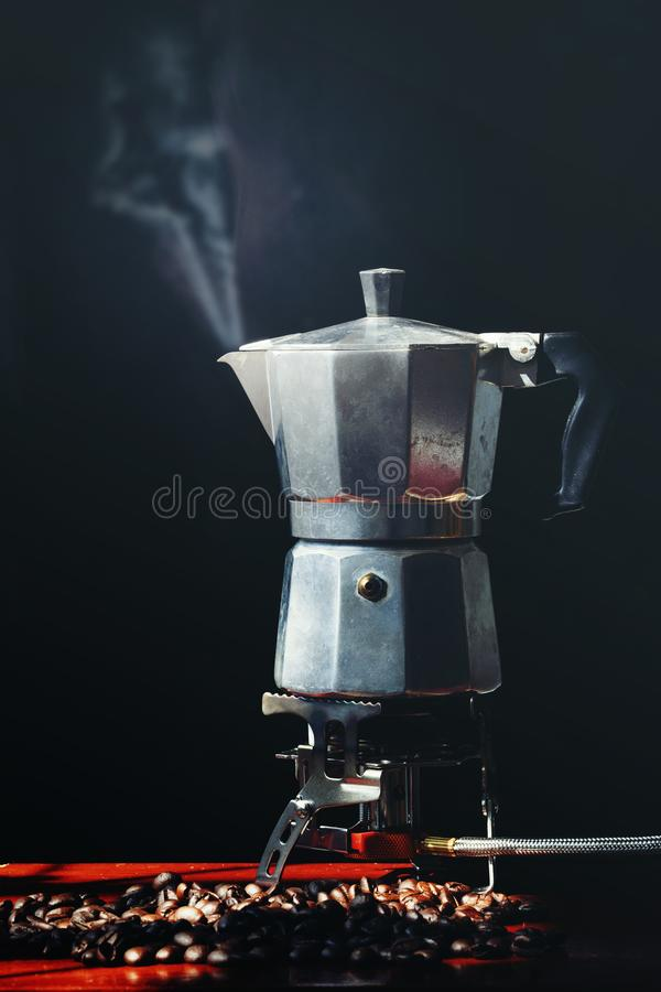 Moka pot old coffee maker and coffee beans. On black background royalty free stock image