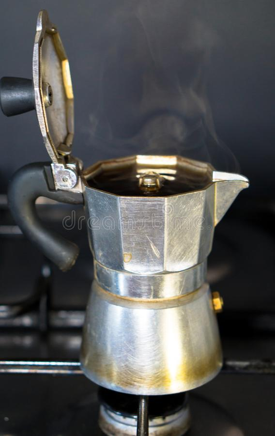 Moka on the stove.Italian traditional old coffee maker. With hot espresso coffee inside, open a coffee pot, steam comes out of the coffee pot, close-up royalty free stock photography