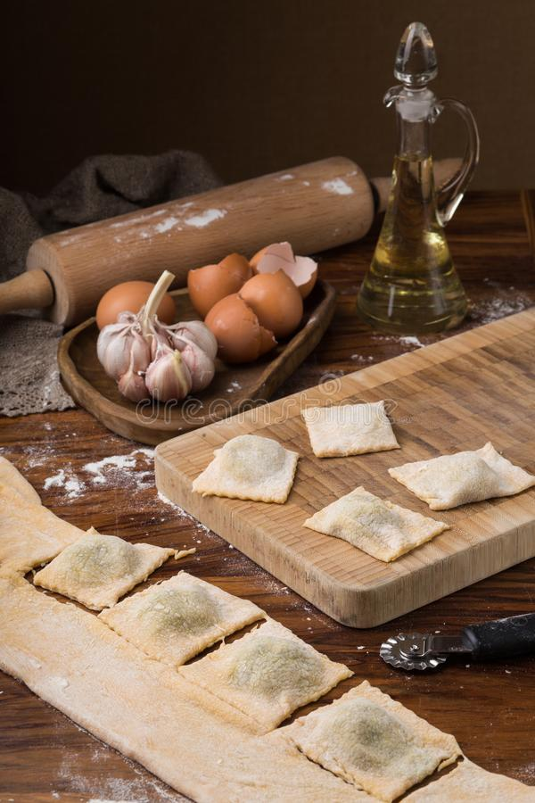 Mokbloem, eieren, deegrol, olijfolie in een kruik op een houten achtergrond, die ravioli maken royalty-vrije stock afbeeldingen