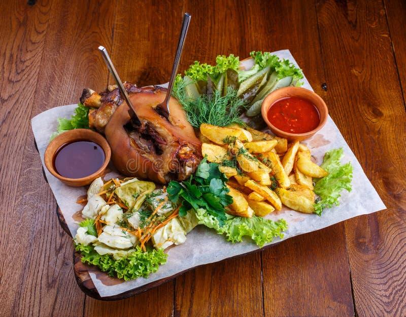 Moked猪肉腿用土豆、酱瓜、圆白菜、荷兰芹、沙拉、莳萝和红色调味汁 免版税图库摄影