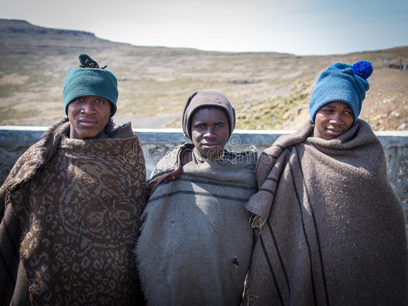 Mokhotlong, Lesotho - September 11, 2016: Three unidentified young African sheperds in traditional thick blankets royalty free stock images