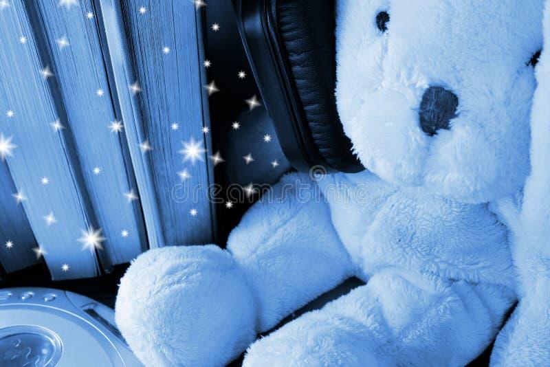 Mokiet zabawka jest ubranym zbyt dużych hełmofony siedzi wśród pozycji rezerwuje Błękitny nocy gwiazdy skutek zdjęcie stock