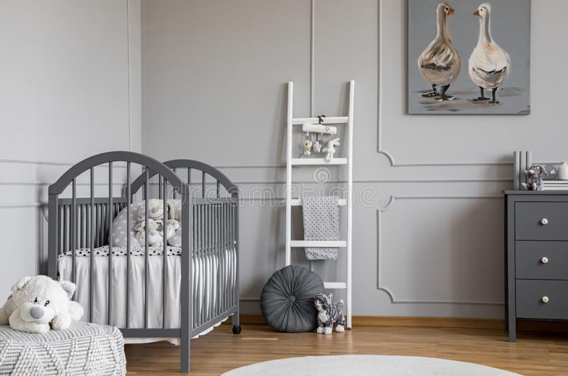 Mokiet zabawka na pouf przed popielatym łóżkiem w dziecko sypialni wnętrzu z drabiną i plakatem Istna fotografia obraz stock