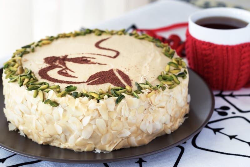Mokka kawa ablegrujący tort z masło śmietanką, pistacja, kubek w czerwonej dzianiny koszula, zakończenie bielu tło Wygodny Bożena obrazy stock