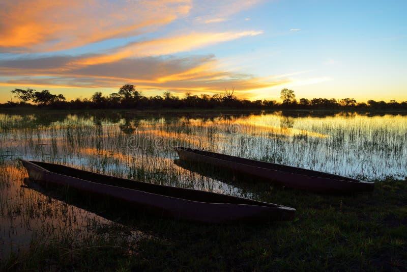 Mokoro en el delta de Okavango en la puesta del sol, Botswana imagen de archivo libre de regalías