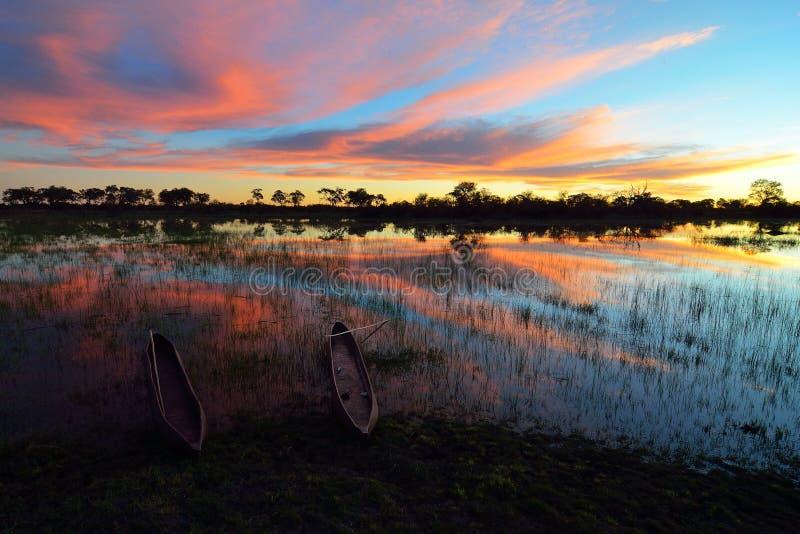 Mokoro en el delta de Okavango en la puesta del sol, Botswana imagen de archivo