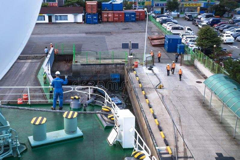 Worker at deck waving for docking with the ferry from Jeju at Mokpo harbor, Mokpo, South Korea stock photo