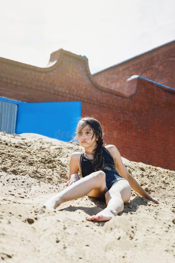 Mokra dziewczyna z ciemnym włosy w czarnym kostiumu kąpielowym kłama na piasku po pływać w rzece fotografia stock