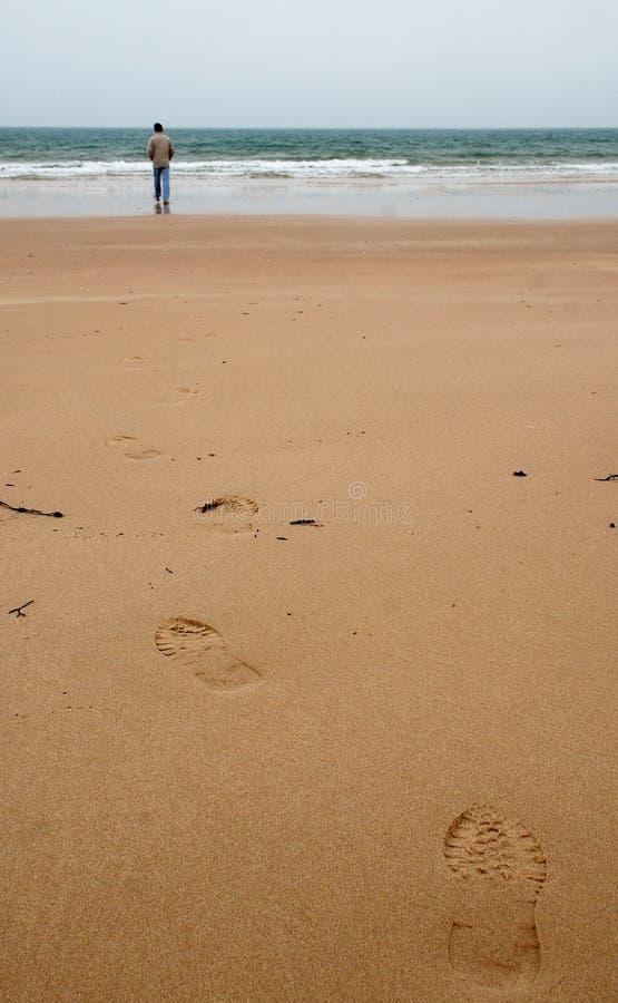 Mokra piasek plaża z odciskami stopy i dalekim mężczyzna obraz stock