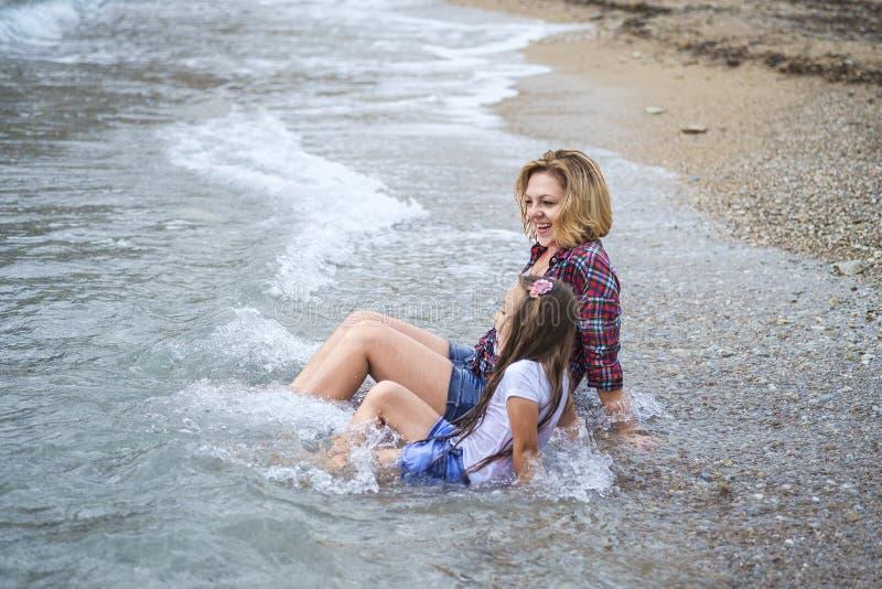 Mokre dziewczyny siedzi w wodzie na morzu wyrzucać na brzeg obraz royalty free