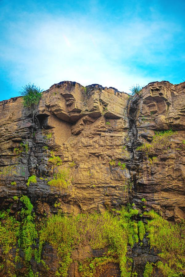 Mokrego hard rock Pionowo faleza z Wodnym Seepage i niebieskim niebem obraz stock