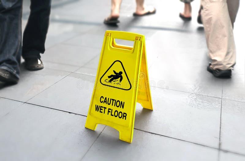 Mokry podłoga znak z ludźmi chodzi w tle zdjęcie stock