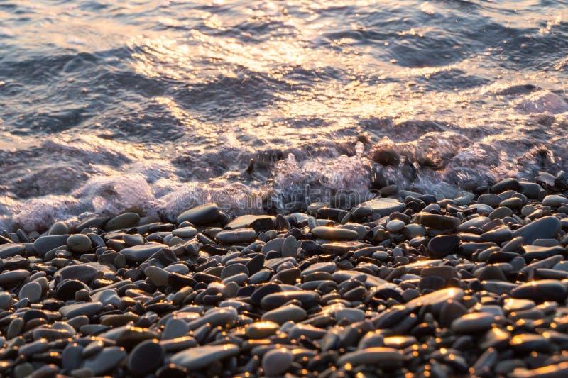 Mokrzy błyszczący kamienie i mała fala na plaży obraz stock