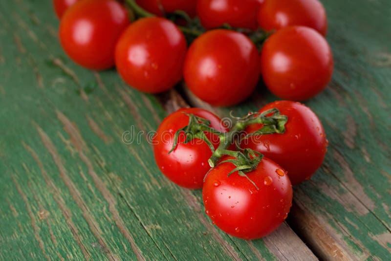 Mokrzy dojrzali soczyści pomidory na zielonym stole zdjęcia royalty free