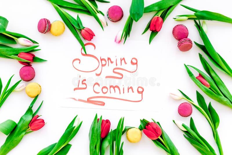 A mola é rotulação de vinda da mão cercada por macarons vermelhos das tulipas e dos doces na opinião superior do fundo branco imagens de stock