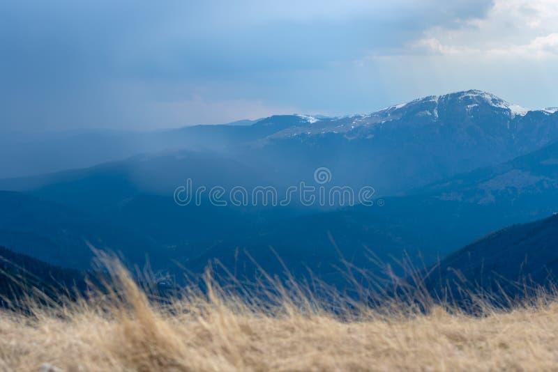 Mola adiantada nas montanhas, com os picos ainda cobertos com a neve Vista panorâmica de uma paisagem alpina natural em um dia en fotos de stock royalty free