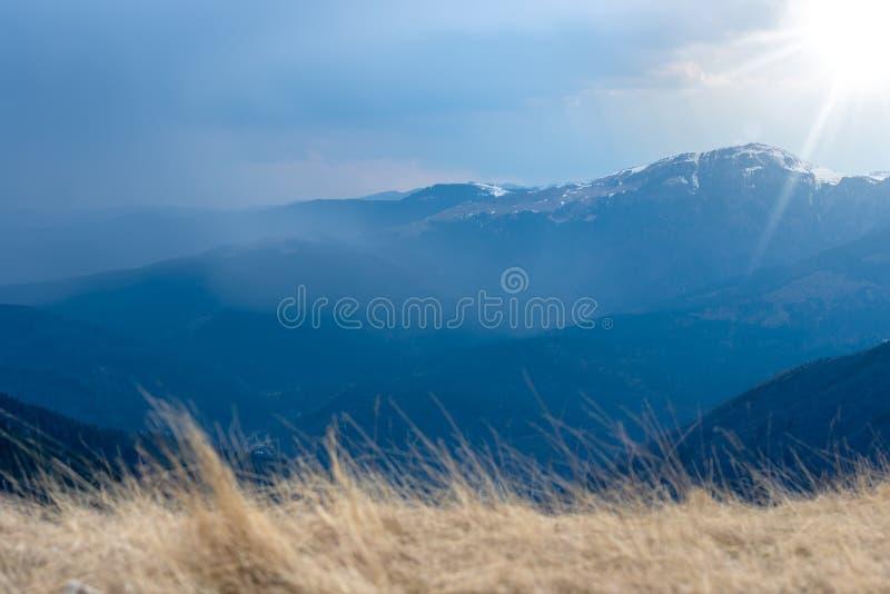 Mola adiantada nas montanhas, com os picos ainda cobertos com a neve Vista panorâmica de uma paisagem alpina natural em um dia en fotografia de stock