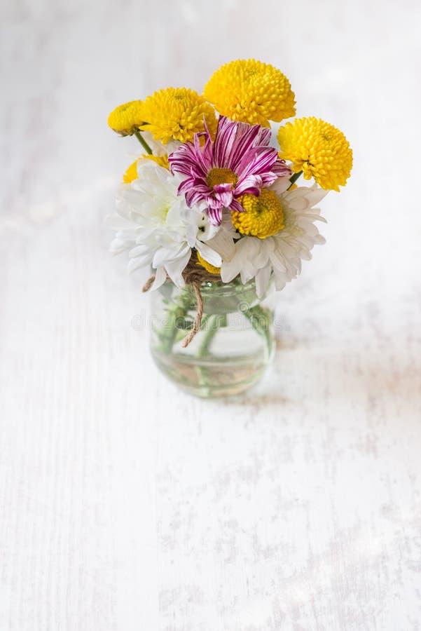 A mola floresce o ramalhete em um vaso do frasco em um fundo rústico de madeira branco fotos de stock royalty free