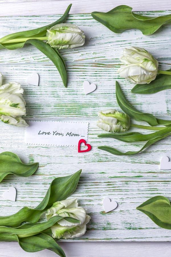 A mola floresce tulipas e o coração vermelho em um fundo claro Dia do `s da matriz Ame-o, mamã imagens de stock royalty free