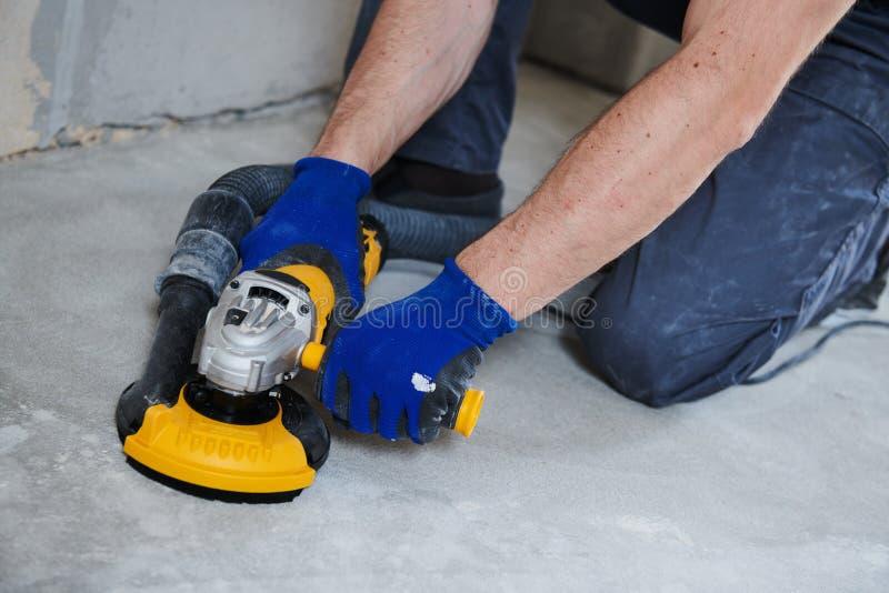 Molatura concreta del pavimento dalla macchina della smerigliatrice di angolo immagine stock