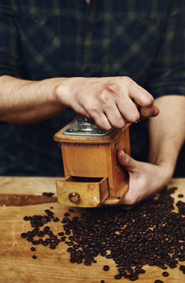 Molatura maschio sui chicchi di caffè fotografia stock