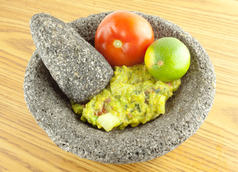 Molcajete Mortar Bowl and Pestle Filled With Guacamole And Ingredients. Molcajete mortar bowl and pestle filled with guacamole, tomato,and lime on a wooden table stock photography