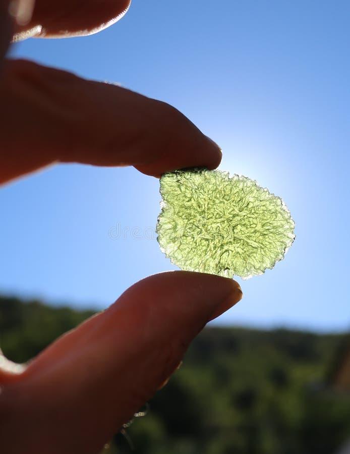 Moldavitekristal die in de zon glanzen stock afbeelding