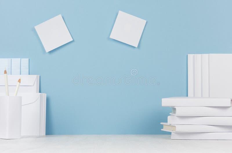 Molde da escola - livros brancos, artigos de papelaria, etiquetas vazias na mesa branca e fundo azul macio fotografia de stock