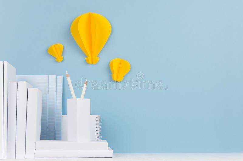 Molde da escola - livros brancos, artigos de papelaria, origâmi amarelo de papel decorativo das ampolas na mesa branca e fundo az fotografia de stock royalty free