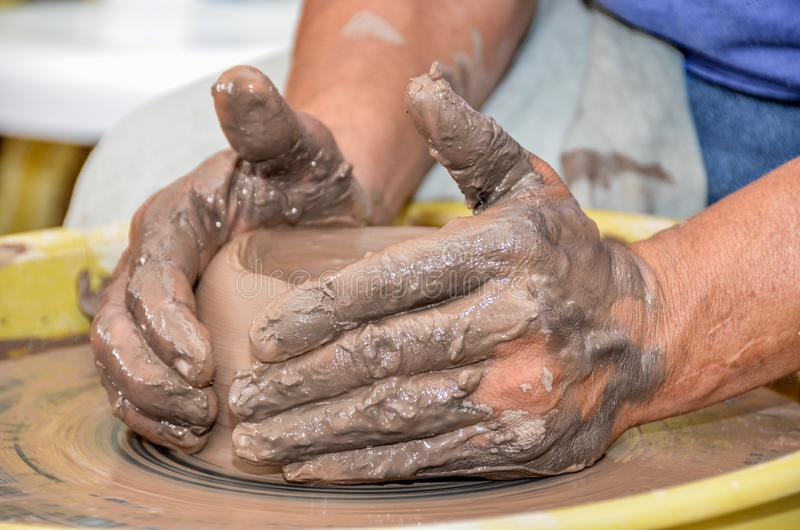 Molde de mãos da escultura do artista que faz a cerâmica da argila na roda fotografia de stock
