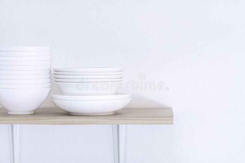 Molde de madeira da prateleira isolado no fundo branco da parede que ajuste sobre bacias e placas brancas empilhadas como utensíl imagens de stock
