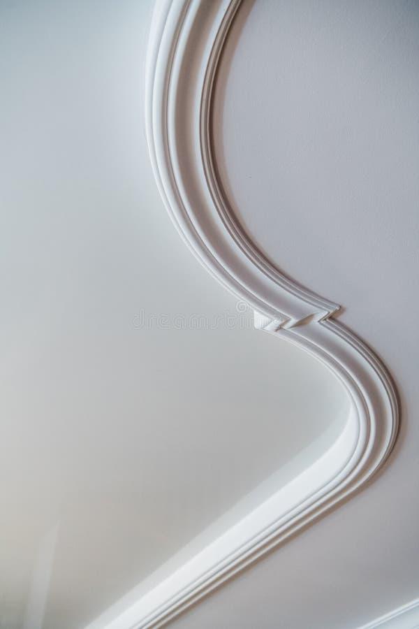 Molde decorativo curvado do relevo do estuque da argila no teto branco no interior clássico abstrato do estilo imagem de stock