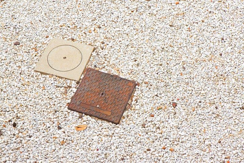 Molde del hierro y bocas concretas en una nueva pavimentación de la grava vista de fotografía de archivo