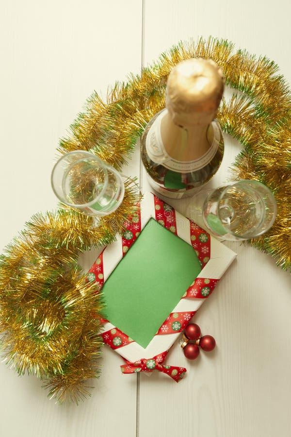 Molde do cartão feito de dois vidros e garrafas do champanhe com as bolas que penduram na fita, no ouropel e no cartão com bobina fotografia de stock