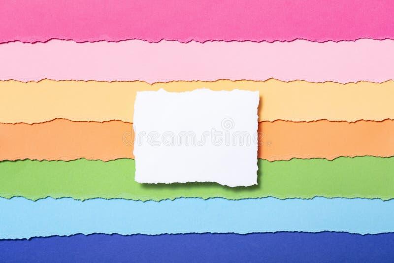 Molde para escrever o texto no centro, um pedaço de papel branco em um fundo listrado multi-colorido de tiras rasgadas do cartão fotos de stock